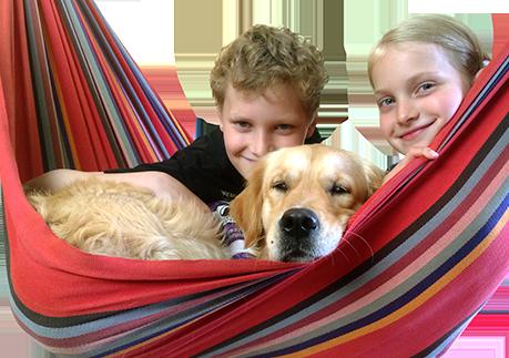 Kinder mit dem Therapiebegleithund Kalle in der Hängematte